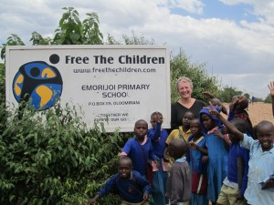 Glenda Black in Kenya with some children posing by a Free the Children sign